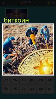 из земли рабочие достают огромной величины монету биткоин