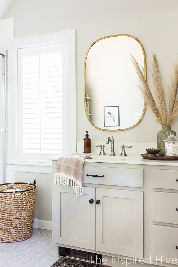 Master bathroom with grey vanity, gold mirror, nickel faucet, plantation shutters, and hyacinth basket laundry hamper