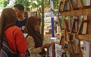 Membaca koleksi yang terpajang di stand Taman Baca Mandiri
