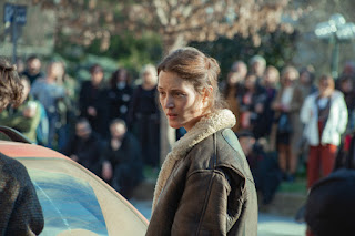 Vicky Krieps in character wearing a brown leather flying jacket