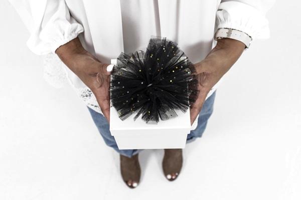 Mulher em um fundo branco segurando uma caixa de presente nas mãos
