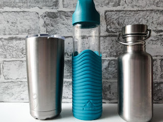 You can see 3 cups/ bottles lined up on a white surface with a grey brick wall background. On the Left you can see a large silver tumbler with a clear lid and a chilly shape engraved near the bottom. The middle is a glass bottle with a blue silicone cover that has a wave like design carved into it in stripes and the bottle has a blue lid. The final bottle on the right is a silver bottle with a small neck that leads to a round screw on lid with a handle to hold onto