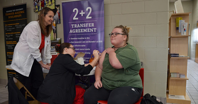 woman receiving a flu shot from a nursing student and an instructor
