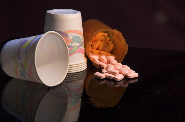 A stack of small paper water cups and aspirin.