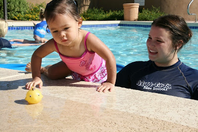 Piture of a swim teacher in the pool coaching a toddler on the side of the pool after a toy duck: Swim Lessons Won't Keep Your Toddler From Drowning