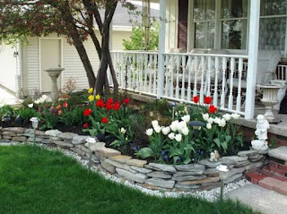 A beautiful bed embraced by grey stones below a front porch with white railing.