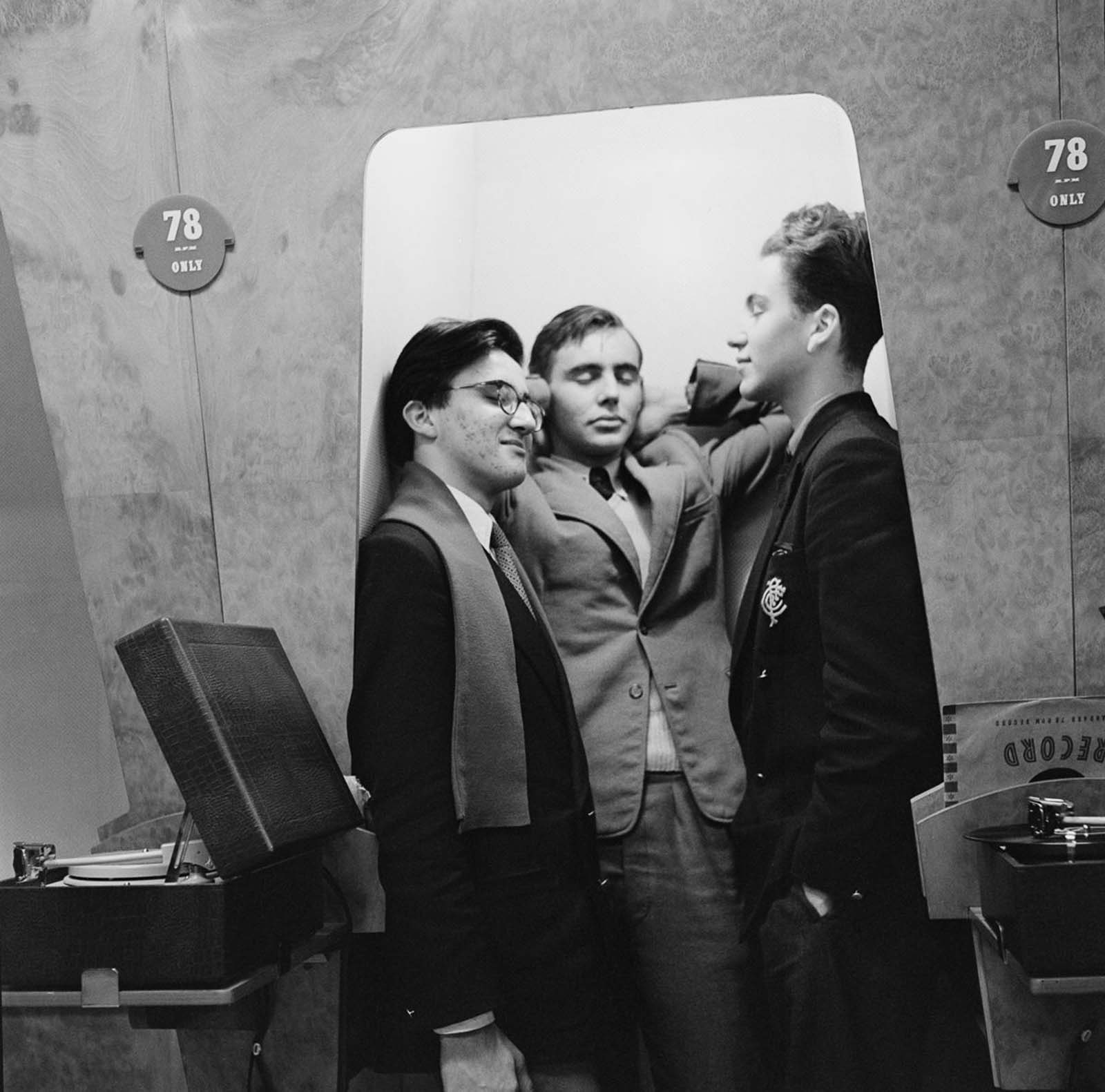A group of friend enjoying music in a listening booth. 1955.