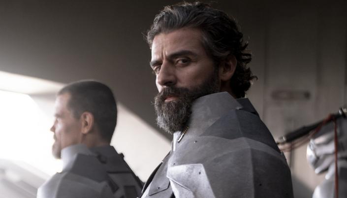 Imagem: o personagem Duque Leto, interpretado por Oscar Isaac, um homem com cabelos escuros e barba com fios grisalhos em uma armadura cinzenta em uma espécie de hangar ao lado de outros guerreiros.