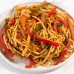 Square image of a plate of noodles with vegetables