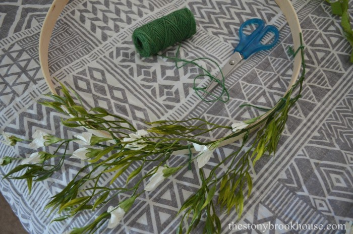 Tie greenery to embroidery hoop