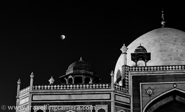 Recently some of my friends had permissions to visit various monuments in Delhi to shoot Lunar Eclipse on 10th Dec, 2011. I also joined them, although all the hard-work for planning these photo-shoots, getting permissions and arranging appropriate equipments was done by other folks. All photographs shared here are not related to the project. These are some of the casual shots taken during eclipse hours on that evening...Here is one of the simple shot when eclipse just started This shot was taken around 6:35 pm on 10th Dec, 2011 !!! Usually Lunar Eclipse used to take place in January, when sky is mainly covered with clouds or fog. Since this time, it happened early, people got to see it clearly and there was huge buzz among various Photography communities.Here is one of the photograph of Humayun's tomb. It's taken with Zoon-in/Zoom-out during long-exposure. Since most of folks were busy on eclipse project and they had to spent 4 hrs at Humayun's tomb, I thought of roaming around and having some clicks of the place in this wonderful lighting, which is rare to capture. Above photograph is also a result of some of the experiments done at Humayun's Tomb, Delhi.Here are some water ponds in all four directions of Humayn's Tomb, but the one in front of entry gate is maintained well. Reflection of the main tomb was looking awesome in Eclipse hours, although above photograph failed to show the real magic... You can see the shining moon in the sky and lovely hues of sunset, when exposed this view for a long time.A similar photograph of Humayn Tomb, with some part of it being reflecting on adjoining water stream... Usually Humayun Tomb closes before Sunset, but if someone wants to have access for some specific purpose, permissions are required in advance.Relatively closer look at Lunar Eclipse through Humayun Tomb. Lunar Eclipse of 10th Dec 2011 can be seen in Photographs at http://www.examiner.com/photography-in-national/yesterday-s-total-lunar-eclipse-photos-1 as well !!!Light and colors were changing with every minute. In fact the change was very prominent for folks who were shooting moon close-ups with tele-photo lenses. After one stage, color of moon starts changing to red and again come back natural shade after few hours...Opposite side of Humayun Tomb, Delhi, INDIAThere are various photography techniques are explained on web and some of them are really technical. At the same time, some of them are really easy to get an idea about the concept and light variation trend during the eclipse hours. In my opinion, understanding the concept and applying your ideas is more important otherwise we always see similar shots on every lunar eclipse. Now many softwares even come with standard ways of capturing lunar eclipse and create single HDR or multi-exposure shots.Carrying Gorilla-pod helps in placing camera at low height, so that some of the other compositions can be tried... No doubt that sturdy and big tripods are important for such shoots but some desi fundas also work well :)Humayun Tomb is very well maintained by Archaeological Survey of India !!! ASI is is the organization to get special permissions to get entry into Humayun Tomb in odd hours. There is lot of green area around main tomb in this campus. And there is very special thing about Mughal Architecture that all four areas around a building are maintained in similar fashion. Alignments of landscapes, gardens and trees would be exactly same.During day time, entry fees for SAARC citizens is 10 Rs. SAARC includes Bangladesh, Nepal, Bhutan, Sri Lanka, Pakistan, Maldives and Afghanistan... BIMSTEC Countries  like Bangladesh, Nepal, Bhutan, Sri Lanka, Thailand and Myanmar also need to pay 10 Rs only. For others it's $5.This photograph would be give you a sense about it's shape and architecture. It has a square base and all four faces of Humayun Tomb look same. Theoretically it's a two storey building but height of one storey is unmatchable :) ... Whole building is made of red stone and Taj Mahal is exactly replica of this building, but in white marble...Light streaks touching ground after filtering through tree leaves around Humayun Tomb... Such photographs from early morning look stunning, as light is most favorable at that point of time of the day...Check following link on wiipedia to know more about Humayun Tomb - http://en.wikipedia.org/wiki/Tomb_of_Humayun . This page has rich information about architecture of Humayun Tomb and history related to it.Humayun Tomb is also in the list of World Heritage sites maintained by UNESCO. Check out http://whc.unesco.org/en/list/232 for more details.Every other site about Delhi has special mention of Humayun Tomb, so I would not repeat all those well known facts about the place. Delhicapital.com has also written about Humayun Tomb in a well structured way... Check it out......A photographer sitting in front of main Tomb in the campus to shoot Lunar Eclipse 2011 with Humayun Tomb in foreground. These folks were sitting at same place, fiddling with camera setting to get best possible multi-exposure shots. Some of them also work on HDRs and hope to see the results soon.Some of the standard techniques of shooting Lunar Eclipses are available here - it was lovely evening with enthusiastic Photographers at Humayun Tomb !!!