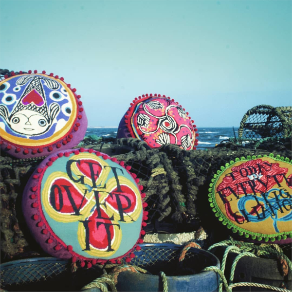 Circular needlepoint cushions with pompom trim by Emily Peacock and Ruan Hoffman