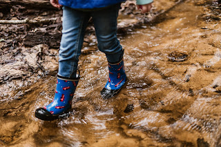 Close up a person in red and blue rain boots and jeans walking in the mud. Photo by Daiga Ellaby on Unsplash