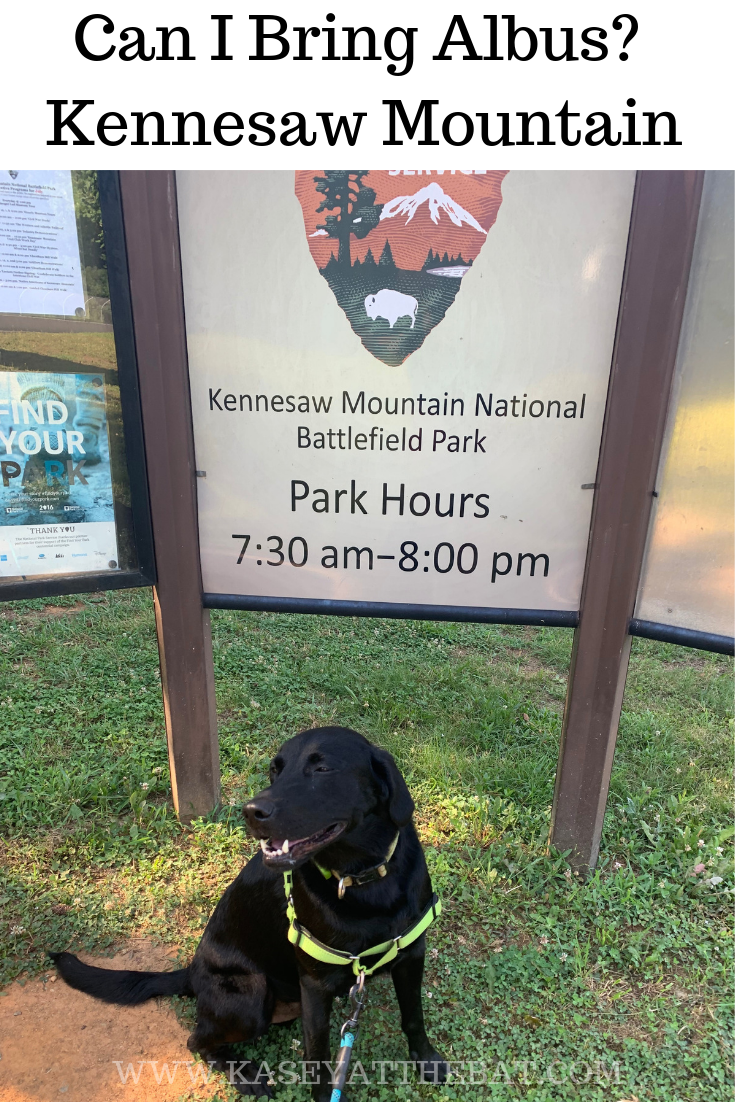 "A black lab stands in front of a sign that says ""Kennesaw Mountain National Battlefield Park"" with park hours below it."