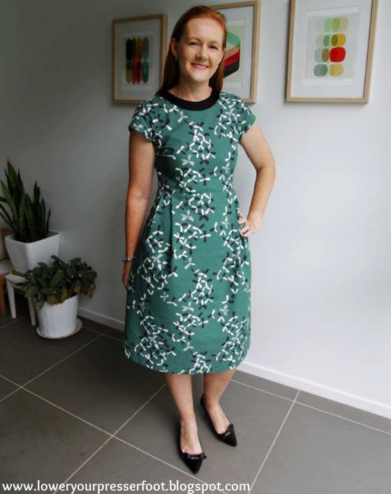 a white lady posing in a green dress standing in front of some plants and wall prints