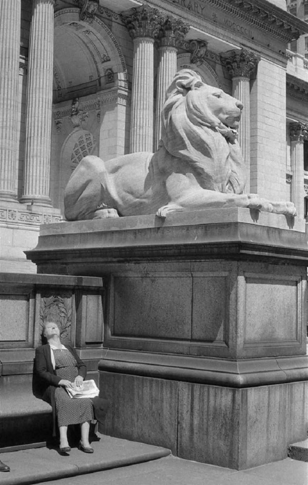 A woman suns herself outside the entrance of the main Public Library building in 1955.