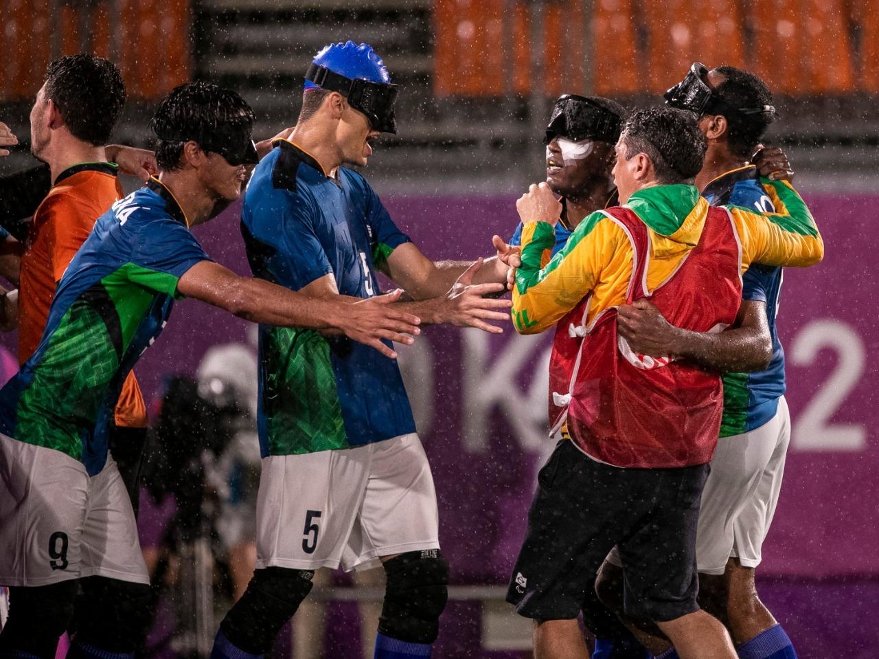 Os jogadores brasileiros, de camisa azul e calções brancos, se reúnem debaixo de chuva para comemorar o gol. Na imagem, Cássio e Tiago, dois homens brancos, estão de braços abertos para abraçar Jeffinho, homem preto, que vai até ao banco de reservas para comemorar com os colegas