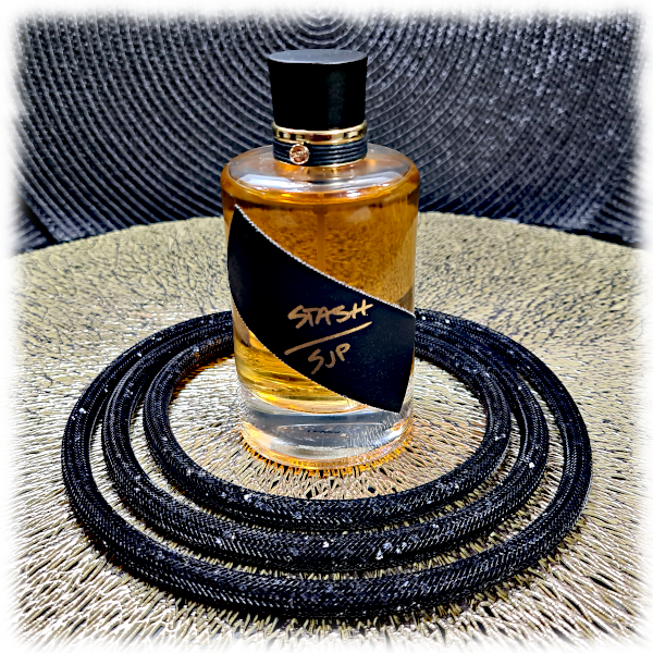 SJP Stash bottle on a gold mesh mat surrounded by a sparkly black choker