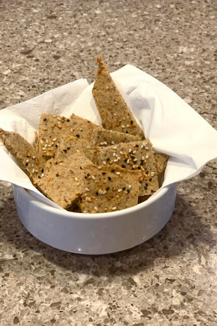 Keto style crackers in a white napkin and bowl.