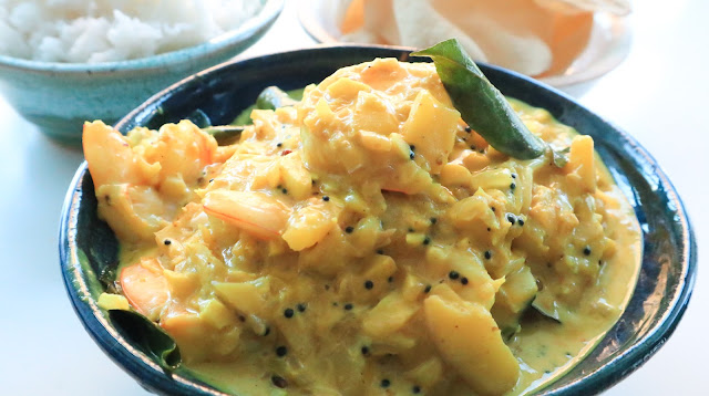 shrimp mango curry in a dark blue homemade wheel thrown bowl, accompanied by rice to the top left corner in a turquoise seagreen bowl and in the top right corner a small white speckled pottery bowl filled with pappadams