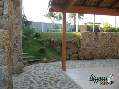Detalhe do muro de pedra com o muro de pedra faceado e o muro de pedra sem cimento com nichos para colocação de plantas, o piso de pedra, os pilares de pedra e a escada de dormente.