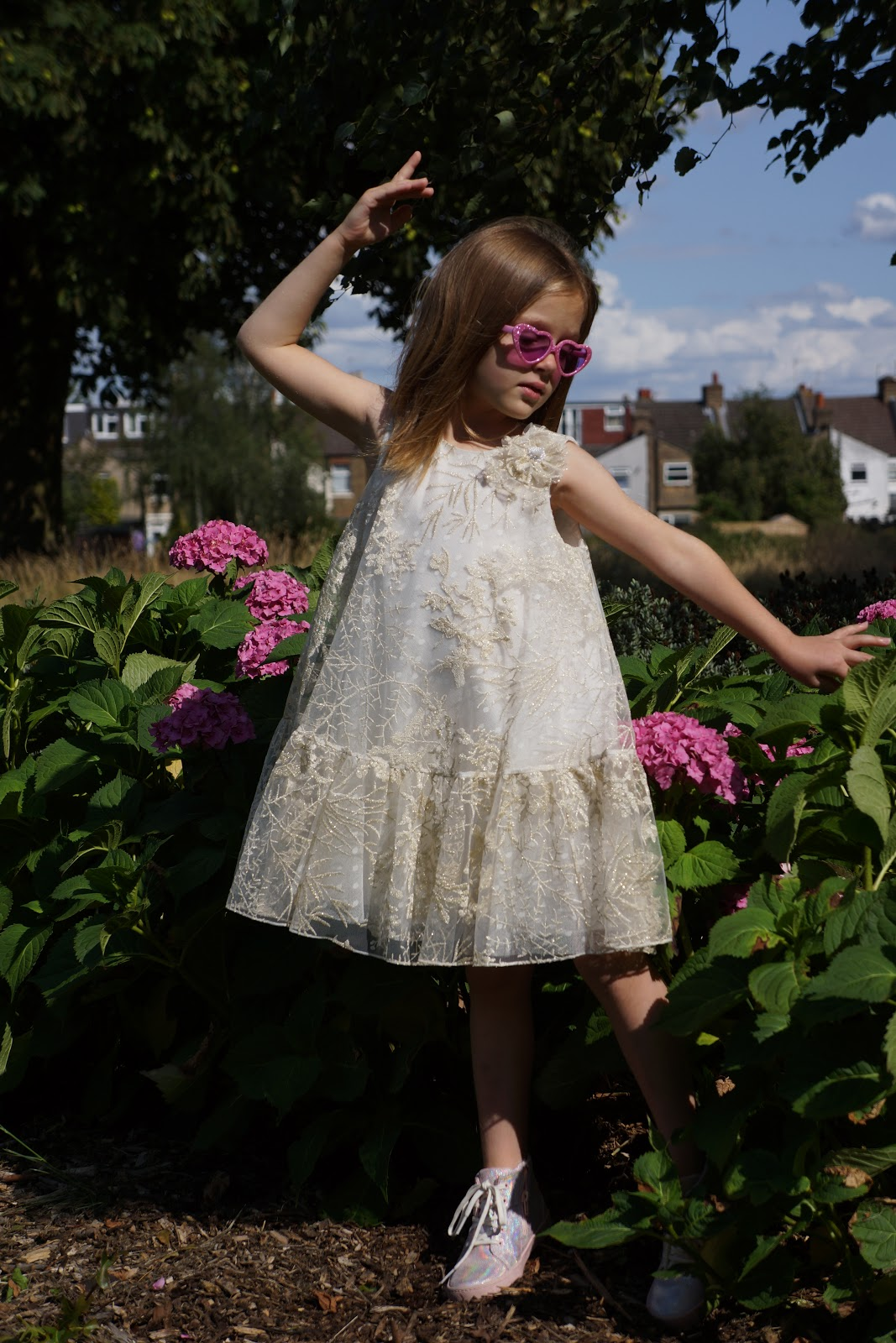 girl in David Charles Childrenswear dress pretending to be a ballet dancer