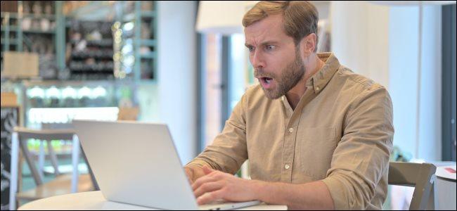 رجل ينظر إلى حاسوبه المحمول بتعبير صادم.
