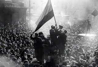 En la Puerta del Sol un grupo de personas se eleva sobre la multitud enarbolando una bandera republicana.