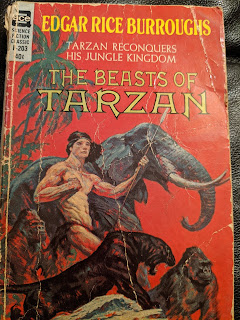 Picture of Tarzan in loincloth, carrying spear, with an elephant, ape and black panther at his side.