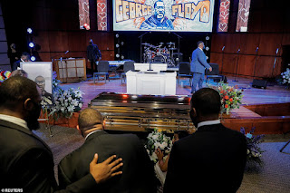Mourners pray over George Floyd's gold casket at his Minneapolis memorial service
