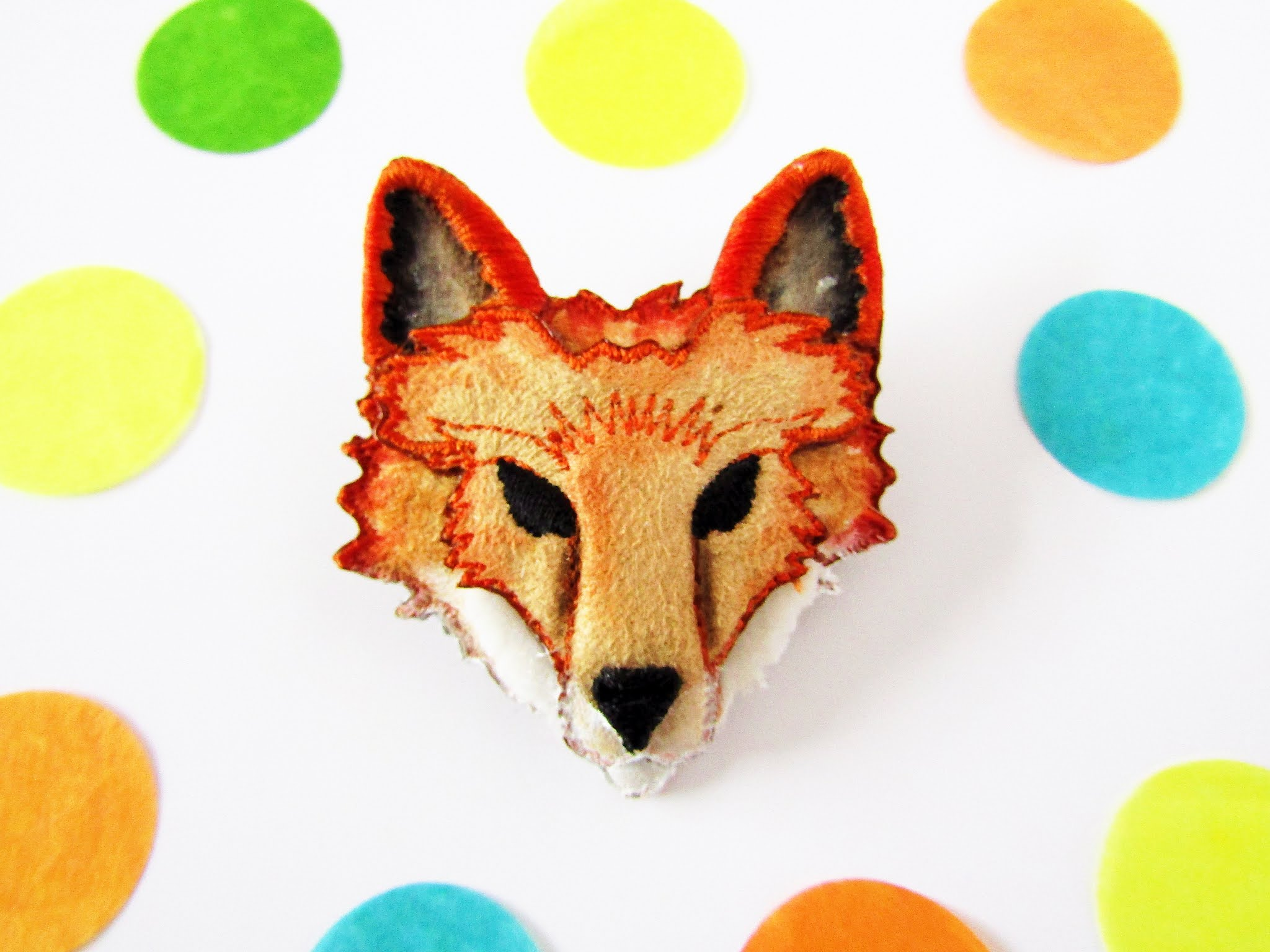A photo of an embroidered red fox brooch.
