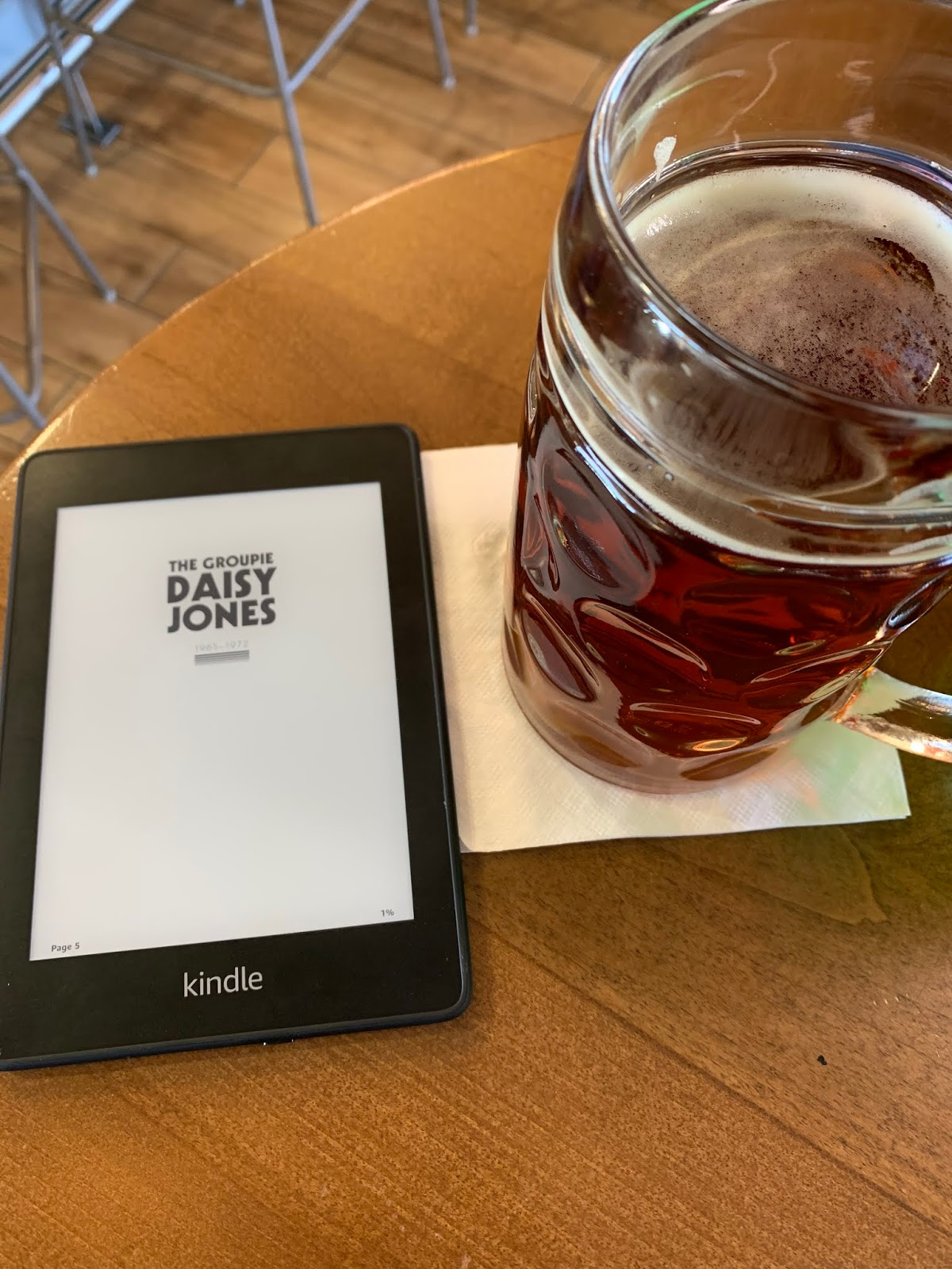 "a kindle with the page ""The Groupie Daisy Jones"" displayed sits next to a mug of beer at an airport bar."