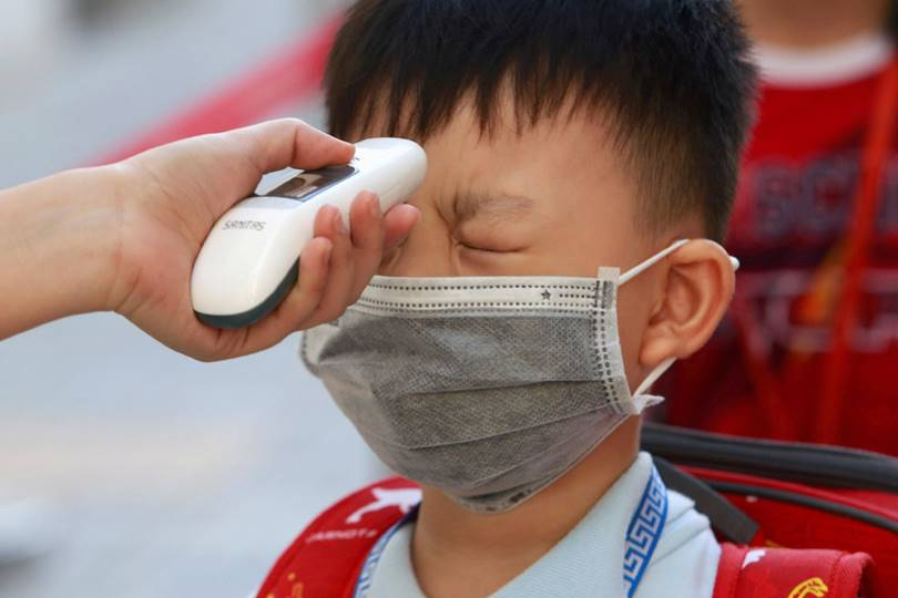 Checking the temperature of an elementary school student. (Photo by Yen Duong)