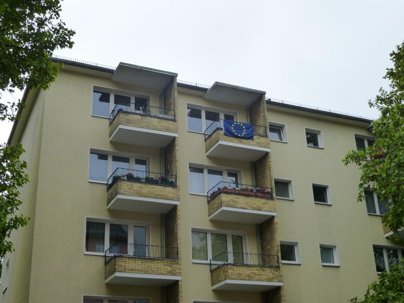 Mehrstöckiges Haus mit Balkonen; an einem einzelnen Balkon ist eine Europaflagge befestigt