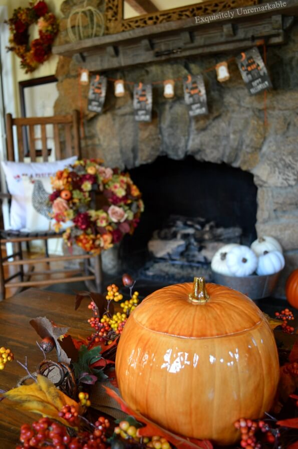 Elegant Fall Decor including a pumpkin cookie jar wrapped in a colorful wreath and a treat bag banner hanging on a stone fireplace