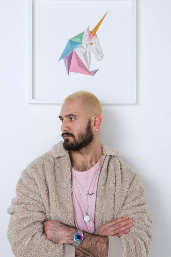 artist Tayfun Tinmaz standing in front of a pastel 3D folded paper unicorn in square white frame hanging on wall