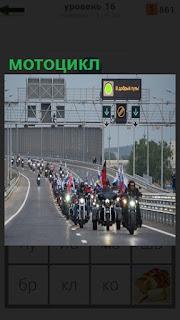 По дороге на мост едут мотоциклисты с флагом с горящими огнями