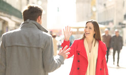 A man with his back to the camera with brown hair and a grey coat waving in the street to a caucasian woman with long brown hair wearing a red coat