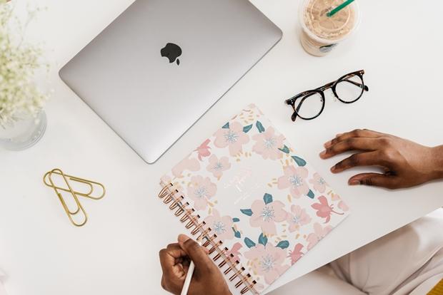 Macbook, agenda, clipes e óculos sobre uma mesa branca