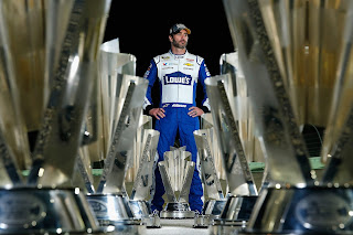 Jimmie Johnson poses with his seven NASCAR Sprint Cup Series trophies.