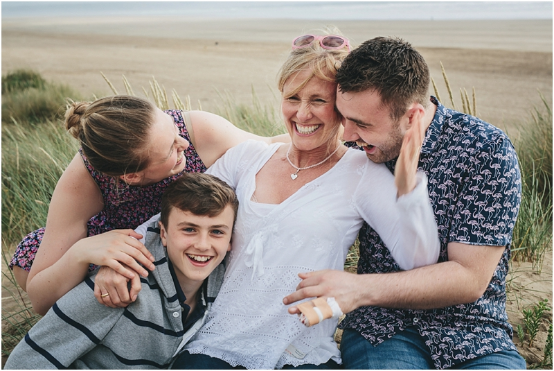 A mother with three adult children laughing together