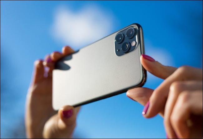 شخص يلتقط صورة بهاتف iPhone