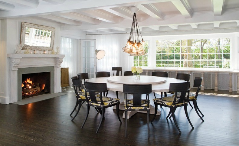 Modern coastal formal dining room with glass bulb chandelier and large round table