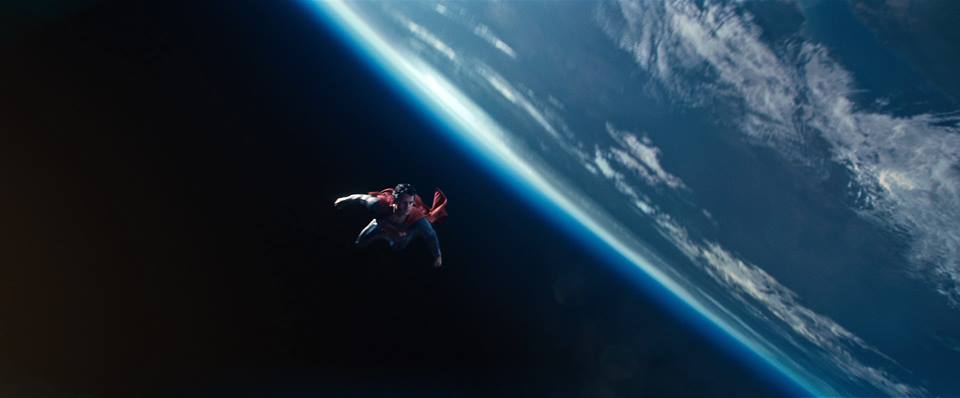 Superman flying above the Earth's atmosphere against the blackness of space