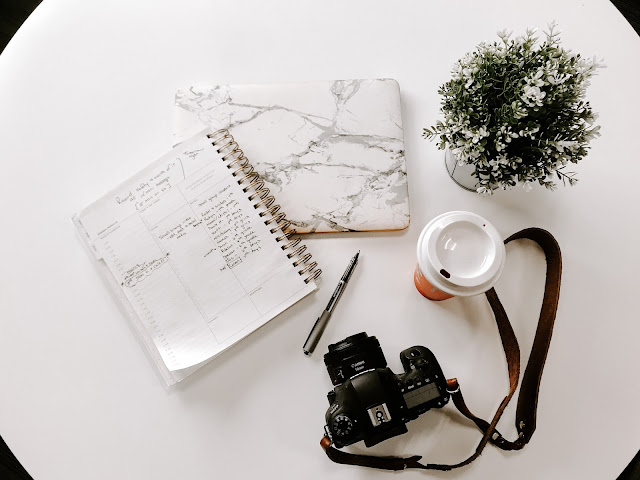 A flatlay featuring a few notebooks, a camera and a vase of white flowers. The note book is marble coloured and the camera has a long strap. There is also a takeaway coffee cup