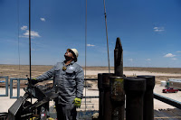A contractor works on a drilling site in the Permian Basin, a massive field stretching from Texas to New Mexico. (Credit: Bloomberg via Getty Images) Click to Enlarge.