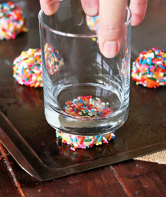 Pressing Down Sprinkle Sugar Cookies Dough Ball with Drinking Glass Image