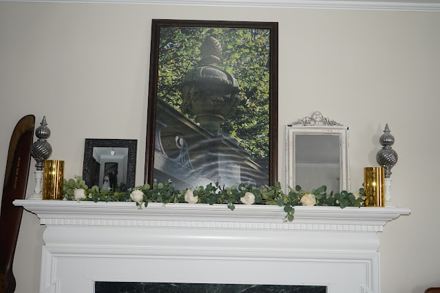 Mantel decorated with rose garland, shabby chic mirror, and photos