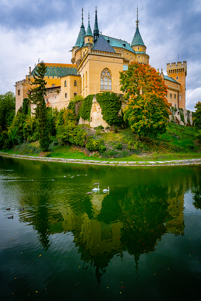 a photo of bojnice castle slovakia with white swans