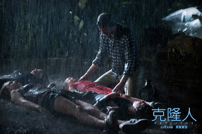 Replicas 2019 movie still showing Keanu Reeves standing over the bodies of his dead family members while it pours rain